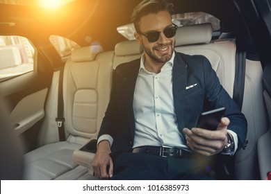 Busy working day. Handsome young man in full suit looking at his smart phone and smiling while sitting in the car