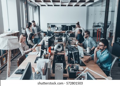 Busy working day in office. Group of young business people in smart casual wear working and communicating while sitting at the large desk in the office together