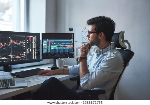 Ein Tag voller Arbeit. Seitenansicht eines erfolgreichen Händlers oder Geschäftsmanns in formaler Verschleiß- und Brillenarbeit mit Diagrammen und Marktberichten auf Computerbildschirmen in seinem modernen Büro