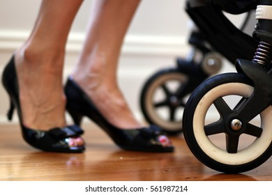 Busy working mother image. Including closeup of the pram stroller and mother in black leather corporate heels pump shoes about to leave for work. Flexible work environment.