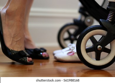 Busy working mother image. Including closeup of the pram stroller, baby shoes and mother in black leather corporate heels pump shoes about to leave for work. Flexible work environment.