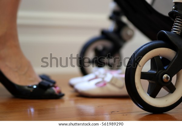 Busy working mother image juggling work and family. Including closeup of the pram stroller and mother in black leather corporate heels pump shoes about to leave for work. Flexible work environment.