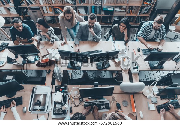 Busy working in office. Top view of group of young business people in smart casual wear working together while sitting at the large office desk