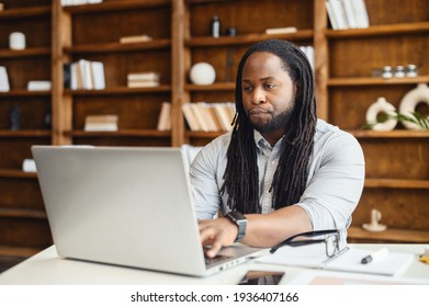 Busy young African-American male office worker with dreadlocks removed glasses sitting at the desk and typing on laptop, student stressing in the library, taking an online exam, working on a project - Shutterstock ID 1936407166