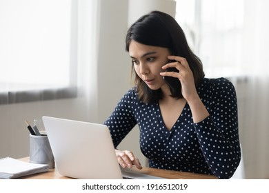 Busy young asian woman work at home office engaged in multitask make phone call check information online using laptop. Skilled vietnamese female agent advisor consult client by cell look at pc screen