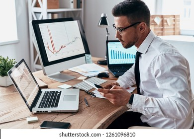 So busy. Young businessman in formalwear using smart phone and analyzing data using computer while sitting in the office
