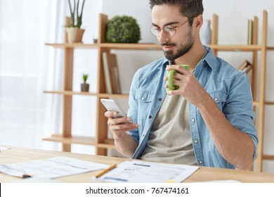Busy young hardworking male sits at working desk, holds smart phone, view photos on Internet, drinks hot coffee or tea from green mug. People, technology and communication concept. Always in touch