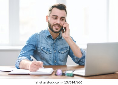 Busy young man in casualwear sitting by desk in front of laptop, making notes in notebook and talking to client on the phone