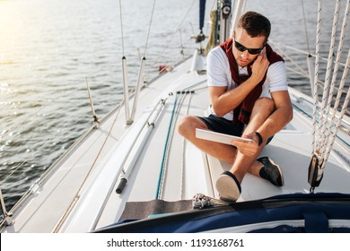 Busy young man sits on board of yacht and talks on phone. Also he holds and looks at tablet. Young man sits with legs crossed. He wears sunglasses.