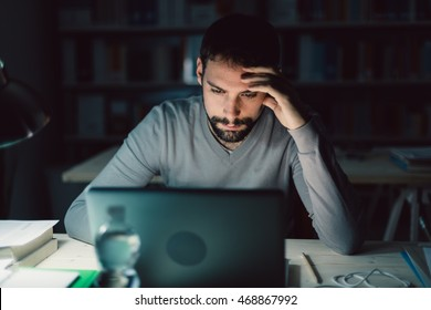 Busy young man working overtime late at night and sitting at office desk, he is using a laptop and connecting to internet