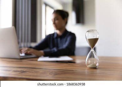 Busy young mixed race woman working studying by laptop on blurred background doing urgent job taking exam. Focus on close up sand glass posed on desk at home office. Measuring time. Deadline is coming