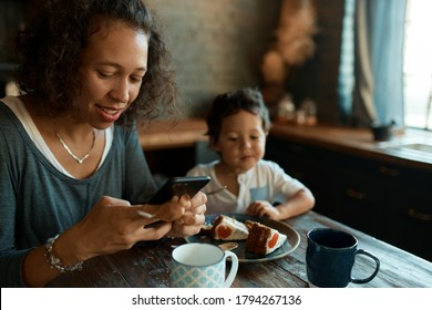 Busy young single mother using cell phone for distant work, writing posts on social network accounts, earning money from home on self isolation, little son sitting at table, eating cake in background