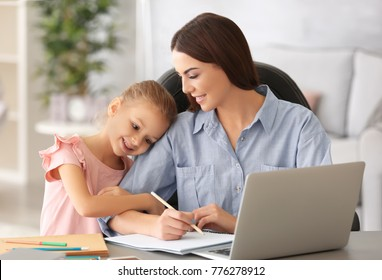 Busy young woman with daughter in home office