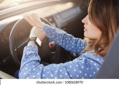 Busy young woman drives car and looks at watch, stuck in traffic jam, hurries to work, being nervous and stressed, feels impatient, keeps hands on wheel. Transportation, vehicle and time concept