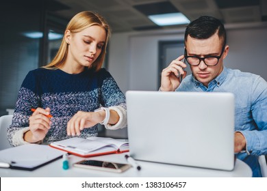 Busy young woman looking at smartwatch and managing time for deadline sitting together with hipster guy at desktop in modern office.Male and female designers cooperating on development of project