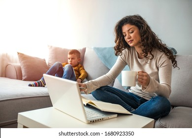 Busy young woman with son at home. Shot of a boy playing while his mother is working on a computer. Young mother with toddler child working on the computer from home
