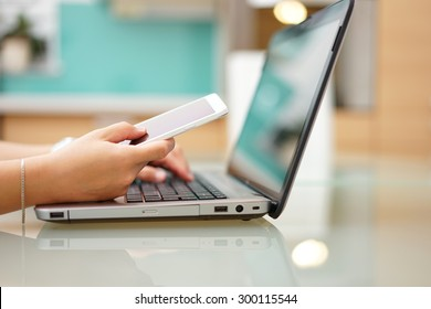 busy young woman is typing on laptop computer and using mobile phone at the same time