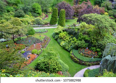 Butchart Gardens in Vancouver Island. Flower beds of colorful flowers and walking paths for tourists. The world-famous masterpiece of park architecture