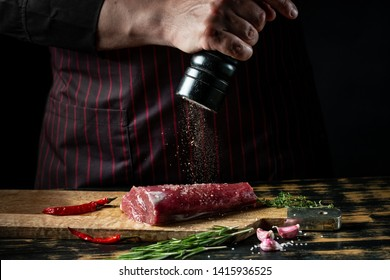 Butcher chef cooking meat fillet and adding salt, pepper and chili for marinade on black background.