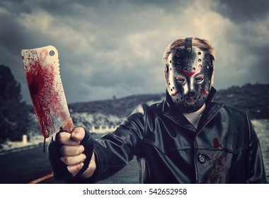 Butcher in hockey mask with bloody meat cleaver