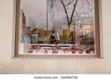 Butcher serving customers seen through the storefront