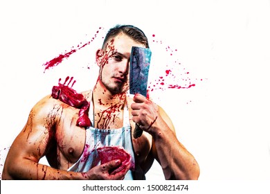 At butcher shop. Butcher chopping red meat. Handsome man cutting raw steak with butcher axe in muscular hands. Strong man wearing butcher apron with blood stains.