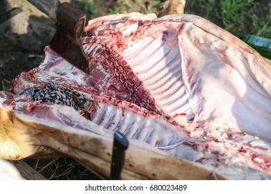Butcher slicing raw pork, home pig slaughtering