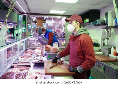 A butcher wearing a coronavirus protective mask. Turin, Italy - March 2020