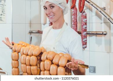 Butcher woman showing sausages on a rail with price