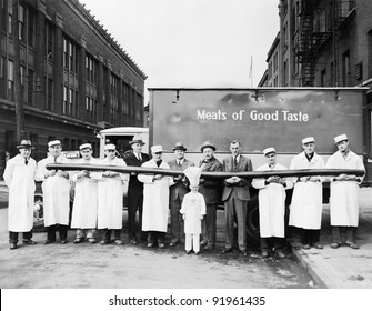 Butchers showing off a long sausage in front of a truck