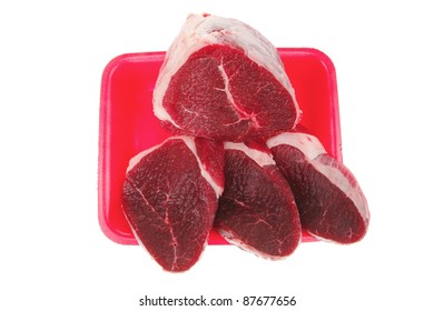 butchery : fresh raw beef lamb big fillet mignon ready to cooking on red tray isolated over white background
