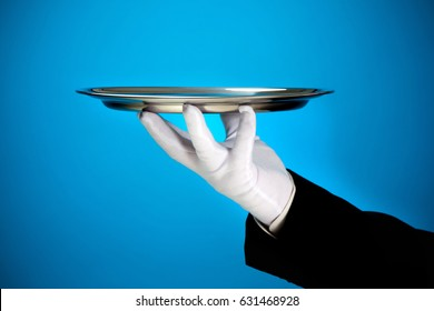 butler holding empty silver tray in white gloved hand