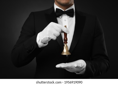 Butler holding hand bell on black background, closeup
