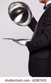Butler lifting the cloche from a silver serving tray, insert your own object onto the tray.