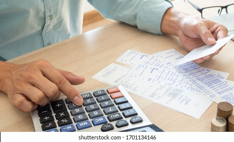 The butler is pressing the calculator calculate the various costs that must be paid by the bill. Many invoices held and placed on the table