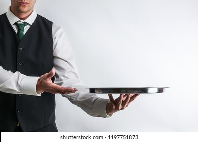 Butler / waiter in white shirt and black suit vest carrying an empty silver tray. Copy space for text on white background.