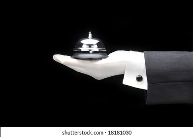 Butlers or concierge holding a service bell in his outstretched hand. Hand and arm only man is unrecognizable.