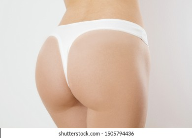 Butt lift and anti cellulite woman body concept. Bikini white panties on female close up isolated on white background. Plastic surgery and liposuction. Cropped image. Skin care and bodycare. Healthy
