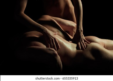 Butt of man. Muscled male model with strong arms. Sexy couple. Fit young guy with beautiful torso. Strong and muscular body of man shaded over black background. Sexy couple. Erotic game play. Massage.