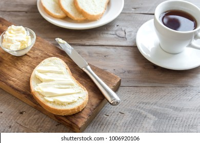 Butter and bread for breakfast, with cup of coffee over rustic wooden background with copy space. Morning breakfast with coffee, butter and toasts.