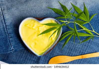 Butter with cannabis plant in a heart shape bowl top view