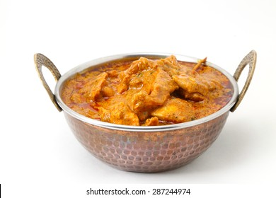 Butter chicken curry, Mutton Curry or Egg Curry isolated on white background in a copper brass bowl.