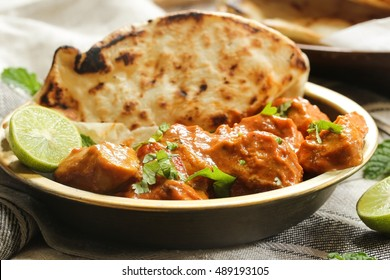 Butter chicken served with Homemade Indian Naan Bread / Murgh Makhani , selective focus