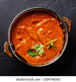 Butter chicken spicy curry meat food in Kadai dish on dark background close-up