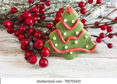 Butter cookie christmas next to holly branch.