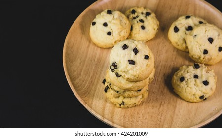 Butter cookies chocolate chips on wood plate on black background with selective focus