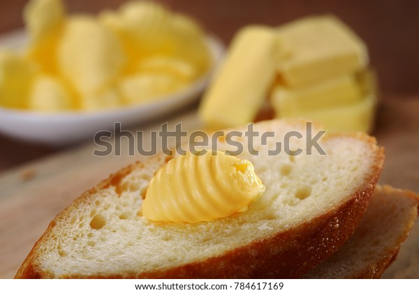 A butter curl on top of a slice of baguette.