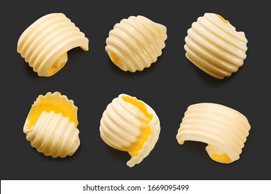 Butter curls isolated on black, top view