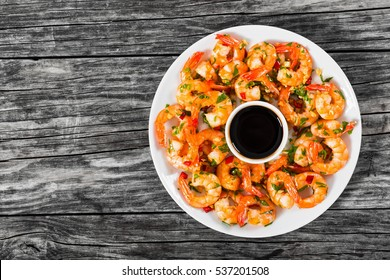 butter garlic fried shrimps sprinkled with pieces of chilli and parsley on white dish with soy sauce in small bowl in centre, on wooden table,view from above