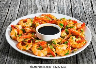 butter garlic fried shrimps sprinkled with pieces of chilli and chopped parsley on white dish with soy sauce in small bowl in centre, on wooden table,view from �°�±�¾�²�µ, close-up